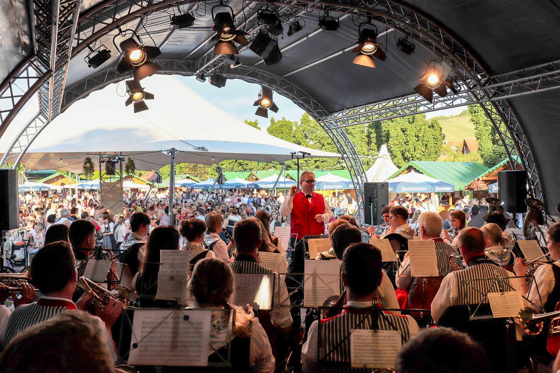 Weinfest_Trachtenkapelle-auf-Bühne-mit-Blick-auf-Dirigent-und-Zelt